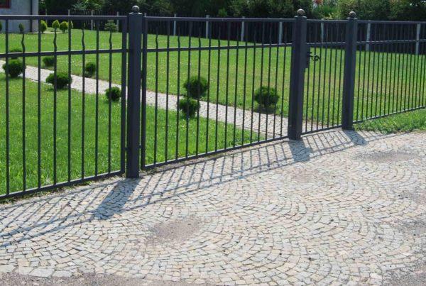 Eleganckie ogrodzenie proste ze słupkami zakończonymi kulami.